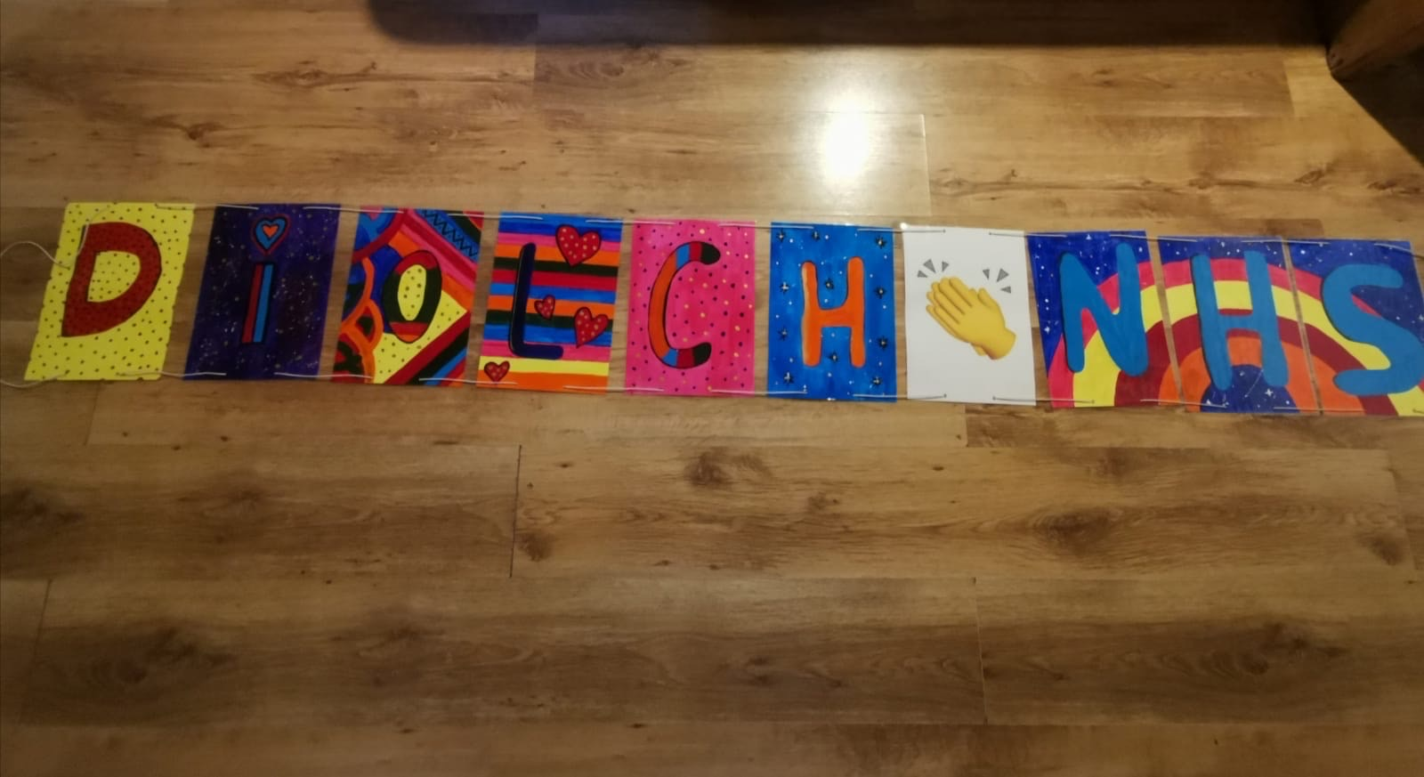 This is a banner made by a 12 year old, each letter has a different coloured background, and it spells out Diolch NHS