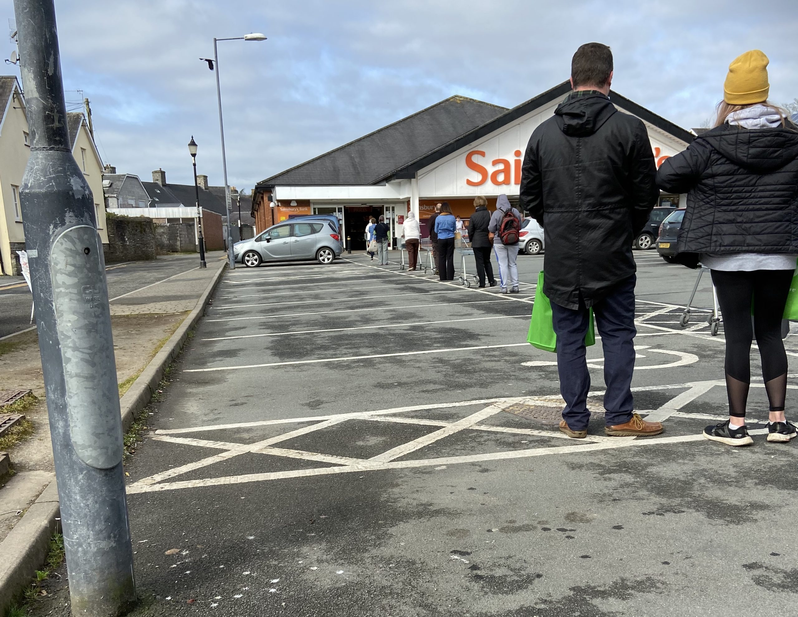 a queue of people in a car park waiting to get in to Sainsbury's