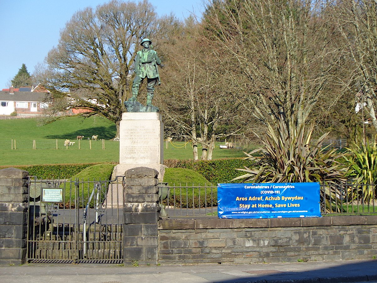 Lampeter War memorial with a sign up saying Stay at Home, Save Lives