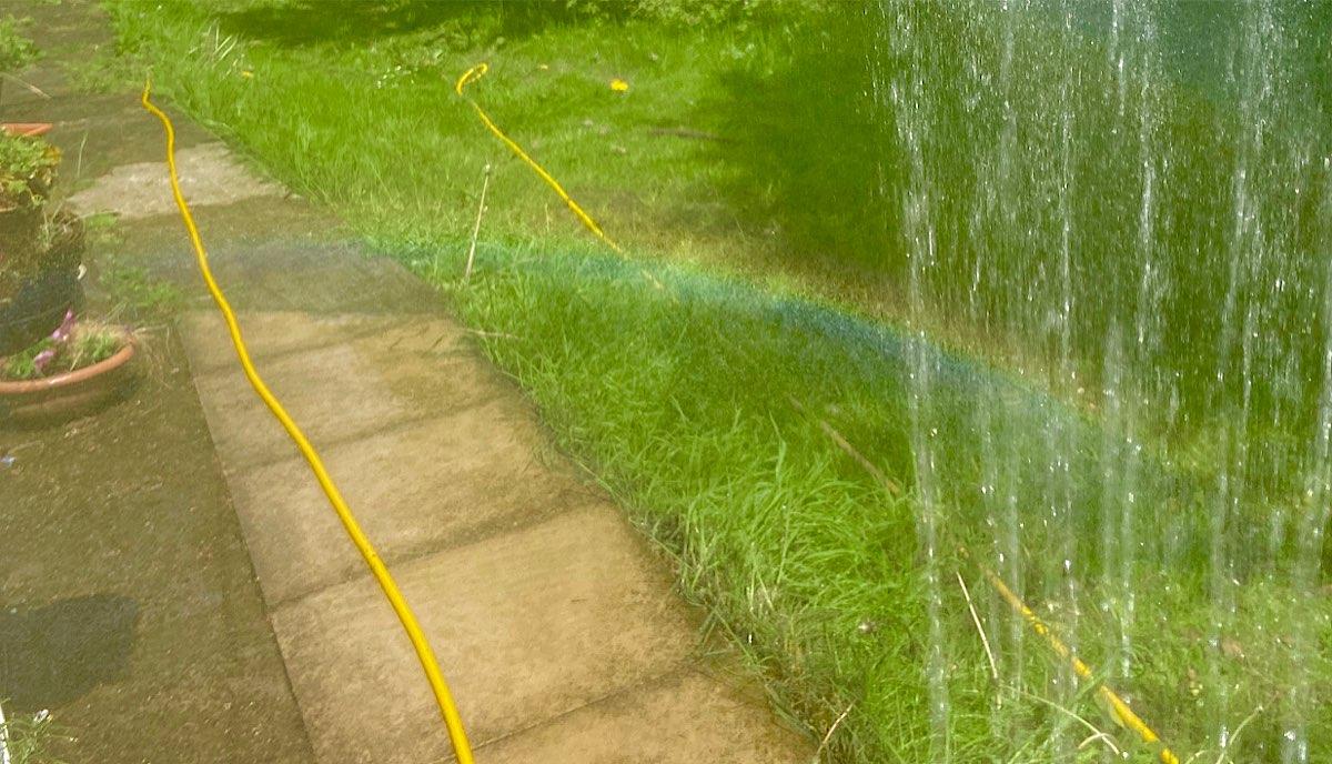 A rainbow created by spray from a hose with the sun behind - it's a rainbow